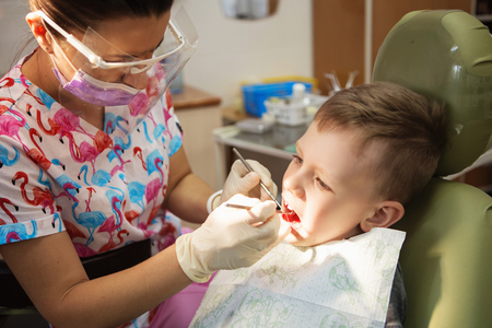 A little boy at a dentists reception in a dental clinic. Childrens dentistry, Pediatric Dentistry. A female stomatologist  is treating teeth of a school-age boy. Oral health and hygiene