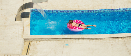 Happy kid playing in blue water of swimming pool on a tropical resort at the sea. Summer vacations concept. Cute girl swimming in pool water. Child with Swimming Equipment - Inflatable Swimming Circle Stock Photo