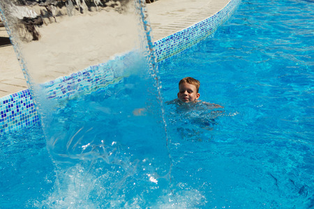 Happy kid playing in blue water of swimming pool on a tropical resort at the sea. Summer vacations concept. Cute boy swimming in pool water. Child splashing and having fun in swimming pool Stock Photo