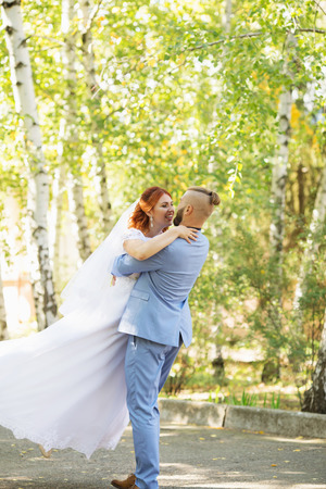 Just married loving hipster couple in wedding dress and suit in the park. Happy bride and groom walking running and dancing. Romantic Married young family. Autumn wedding