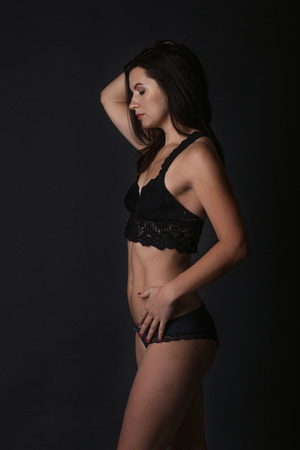 Sexy body of young attractive woman. Beautiful sporty lady in black bikini against dark background Stock Photo