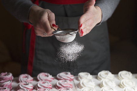 The process of making marshmallow. Close up hands of the chef with metal sieve sprinkling zephyr with powdered sugar at pastry shop kitchen. Stock Photo