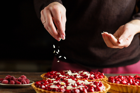 Beautiful freshly made cherry tart decorated with almond chips. Food photography. Process of making tart. Close up hands of the chef sprinkling cake with almond chips at pastry shop kitchen.