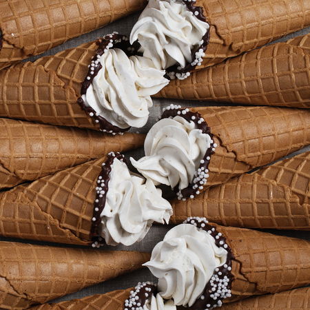 A lot of ice cream cones on wooden table. Soft ice creams or frozen custard in cones. Waffle marshmallow imitating ice cream. Flat lay