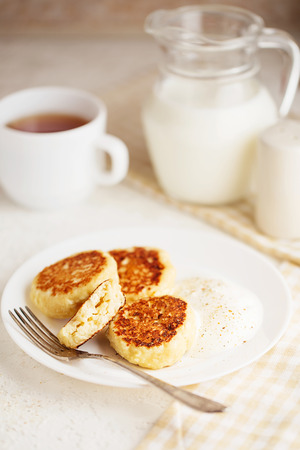 Cottage cheese pancakes with sour cream and tea. Gourmet Breakfast - Cottage cheese pancakes, syrniki, curd fritters in a white plate. Russian syrniki or sirniki, cottage cheese fritters.