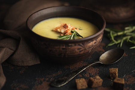 Fish cream soup with Salmon, cheese, Potatoes and herbs in in brown ceramic Soup Bowl. Dark food photography