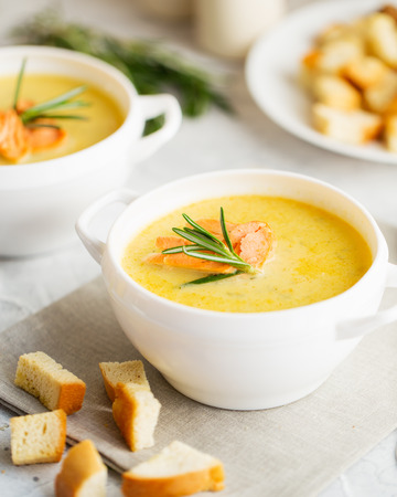 Fish cream soup with Salmon, cheese, Potatoes and herbs in white Soup Bowls. Stock Photo