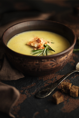 Fish cream soup with Salmon, cheese, Potatoes and herbs in brown ceramic Soup Bowl. Dark food photography