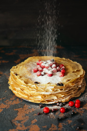 Russian pancakes with berries sprinkled with sugar powder in front of dark background. Pancake week - The ancient Slavic festival of seeing off the winter, from which the custom of baking pancakes