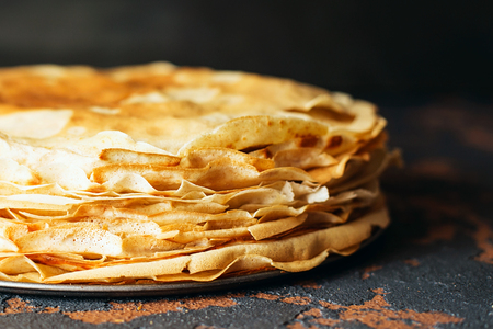 Russian pancakes in front of dark background. Pancake week - the ancient Slavic festival of seeing off the winter, from which the custom of baking pancakes and making fun is preserved.