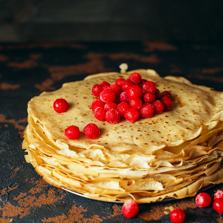 Russian pancakes with berries in front of dark background. Pancake week - the ancient Slavic festival of seeing off the winter, from which the custom of baking pancakes and making fun is preserved.