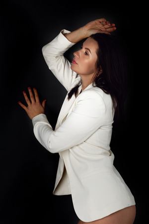 Natural beauty concept. Sexy body of young attractive woman. Beautiful sporty lady in white blazer against dark background