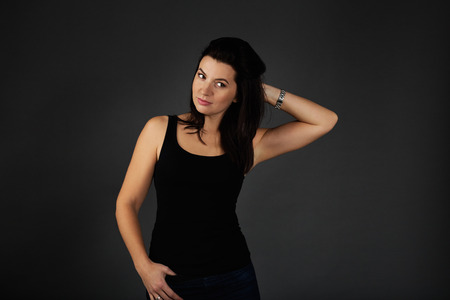 Natural beauty concept. Portrait of young attractive smiling woman. Beautiful sporty lady in black top and blue jeans against dark background