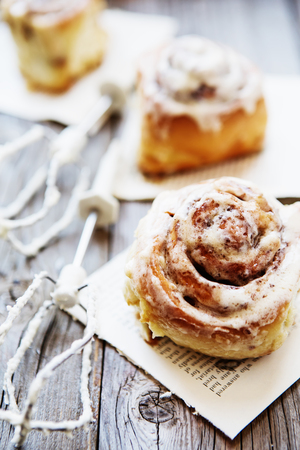 Cinnabon buns. Sinabon rolls with cream cheese and cream, chocolate and almond nuts on wooden background