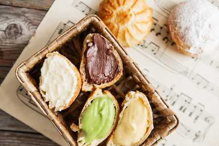 Homemade profiteroles on the music sheet with notes. Profiteroles (choux à la crème) - French choux pastry balls filled with custard or cottage cheese sprinkled with powdered sugar