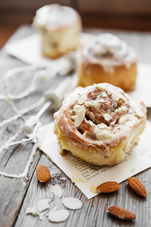 Sinnabon buns. Sinabon rolls with cream cheese and cream, chocolate and almond nuts on wooden background 免版税图像