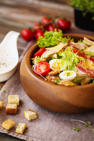 Caesar salad with cherry tomatoes and quail eggs in a wooden bowl Фото со стока