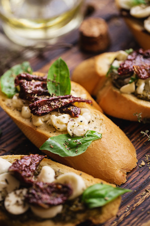 sandwich with mozzarella cheese, pesto, sun-dried tomatoes and basil and thyme, served on the wooden board
