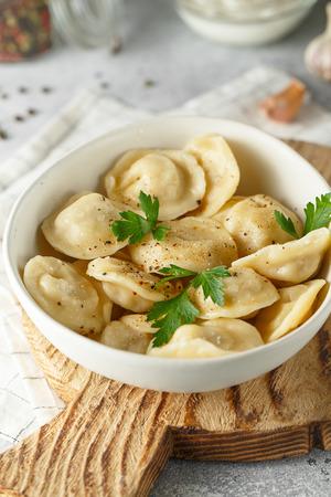 Gnocchi di carne - pelmeni russi, ravioli con carne su un piatto bianco su un tagliere di legno
