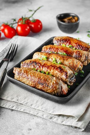 Meat rolls stuffed with Champignon served with tomatoes and green onions in heat-resistant black dish on a gray background. Food photography. Stock Photo