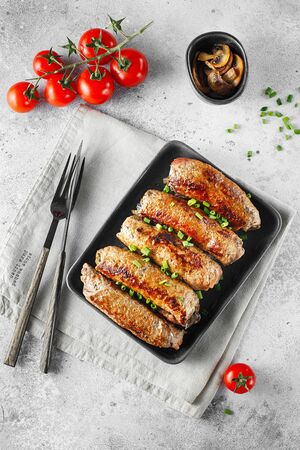 Meat rolls stuffed with Champignon served with tomatoes and green onions in heat-resistant black dish on a gray background. Food photography. Flat lay composition