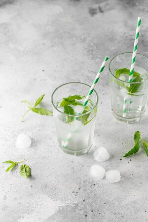 glasses of cold water with fresh mint leaves and ice cubes on grey concrete background. Food photography Stock fotó