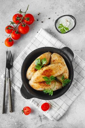 Delicious grilled beef or chicken meatballs. Meat or fish patties on the little frying pan served with parsley and tomatoes. Food photography. Flat lay composition Stock fotó