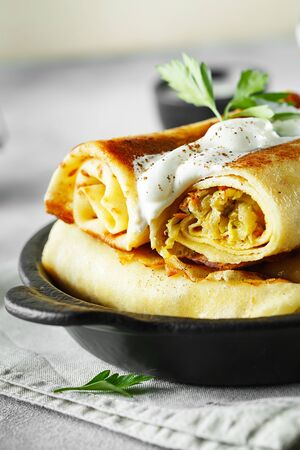 Thin pancakes with fillings. tasty stuffed pancakes crepes with cabbage closeup. Russian Fried Stuffed Pancakes Blintzes with cabbage. Food photography. Stock fotó