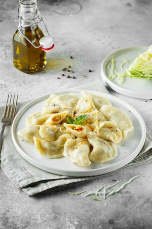 Dumplings, filled with cabbage. Russian, Ukrainian or Polish dish: varenyky, vareniki, pierogi, pyrohy. Food photography.