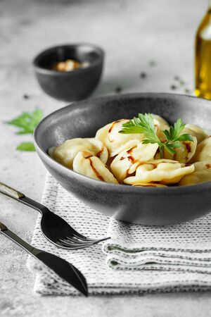 Meat dumplings - russian pelmeni, ravioli with meat on a grey bowl.  Food photography