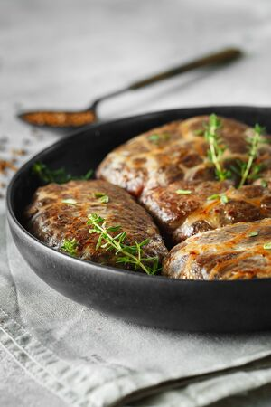 Delicious grilled liver meatballs with buckwheat in a natural casing. Liver patties on the little frying pan served with thyme. Food photography.
