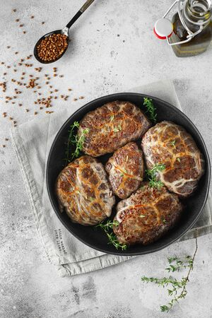 Delicious grilled liver meatballs with buckwheat in a natural casing. Liver patties on the little frying pan served with thyme. Food photography. Flat lay composition Stock Photo
