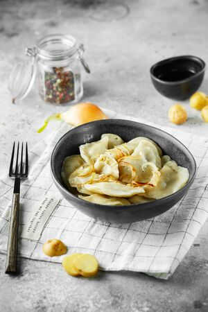 Dumplings, filled with mashed potatoes and onions. Russian, Ukrainian or Polish dish: varenyky, vareniki, pierogi, pyrohy. Food photography.