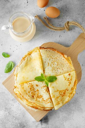 Russian pancakes served with mint leaves and ingredients - milk and eggs in front of grey background. Flat lay composition. Food photography