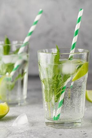 homemade lemonade with lime, mint in a glass on a gray concrete background. Healthy Fresh Mint Water with Lime and ice. Food photography Stock fotó