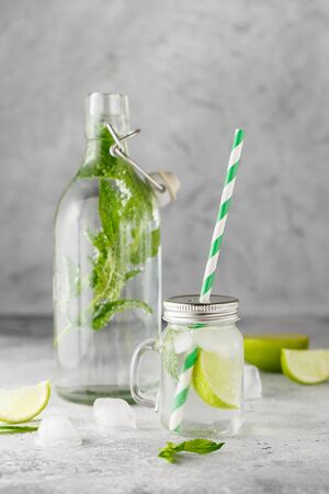 Glass Bottle and lemonade jar with cold lemonade with fresh mint leaves and lime with ice cubes on grey concrete background. Food photography