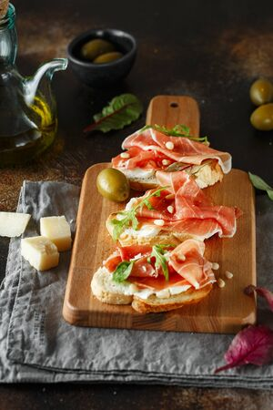 Traditional parma cured ham antipasto. Bruschetta set with Parma Ham and Parmesan Cheese. Small sandwiches with prosciutto, parmesan cheese, fresh arugula, olives and pine nuts on rustic wooden board Reklamní fotografie