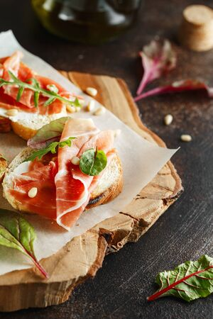 Traditional parma cured ham antipasto. Bruschetta set with Parma Ham and Parmesan Cheese. Small sandwiches with prosciutto, parmesan cheese, fresh arugula, olives and pine nuts on rustic wooden board Stock fotó - 128739082