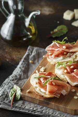 Traditional parma cured ham antipasto. Bruschetta set with Parma Ham and Parmesan Cheese. Small sandwiches with prosciutto, parmesan cheese, fresh arugula, olives and pine nuts on rustic wooden board Stock fotó