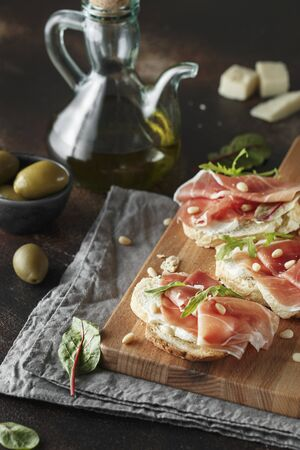 Traditional parma cured ham antipasto. Bruschetta set with Parma Ham and Parmesan Cheese. Small sandwiches with prosciutto, parmesan cheese, fresh arugula, olives and pine nuts on rustic wooden board Stock fotó - 128739096