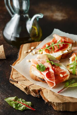 Traditional parma cured ham antipasto. Bruschetta set with Parma Ham and Parmesan Cheese. Small sandwiches with prosciutto, parmesan cheese, fresh arugula, olives and pine nuts on rustic wooden board Stock fotó - 128739231