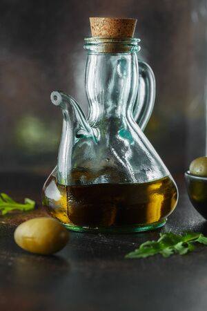 Fresh Organic Olive Oil in the jug on dark background. Food photography. Bottle of tasty olive oil. Glass jug of oil and canned olives