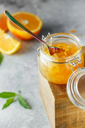 Homemade orange jam in glass jar on the wooden box on the gray background. Orange jam in swing-top jar on wood with orange slices in the back. Food photography. Seasonal cooking concept. Stock fotó