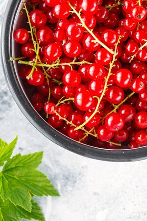Ripe red currant berries in a bowl close up. Fresh ripe red currant on light grey background, top view Stock fotó