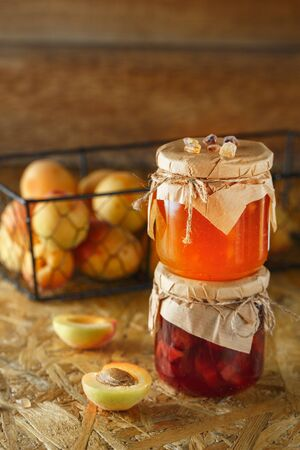 Apricot jam on a wooden rustic background. Two jars of fruit homemade marmalade. Glass jars with different kinds of jam and fruits. Stock fotó