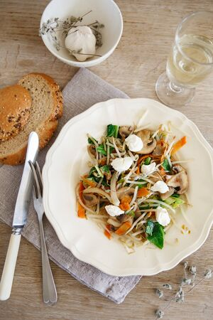 Mixed vegetable stir fry with mushrooms and cottage cream cheese. Tender mushroom stir fry served in a white plate with white wine and bread on the wooden table. Flat lay composition Stock Photo