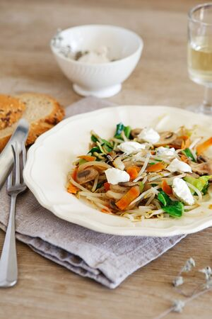Mixed vegetable stir fry with mushrooms and cottage cream cheese. Tender mushroom stir fry served in a white plate with white wine and bread on the wooden table. Vegan food photography Stock Photo