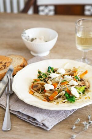 Mixed vegetable stir fry with mushrooms and cottage cream cheese. Tender mushroom stir fry served in a white plate with white wine and bread on the wooden table. Vegan food concept Stock Photo