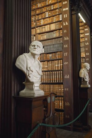 Dublin, Ireland - June 24, 2019: The Long Room interior Of The Old Library At Trinity College. Marble busts of great people and shelves with antique tomes Editorial
