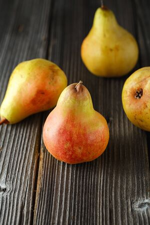 Seasonal fruits. Several tasty ripe juicy pears on a wooden background. veganism, healthy eating and lifestyle concept Zdjęcie Seryjne